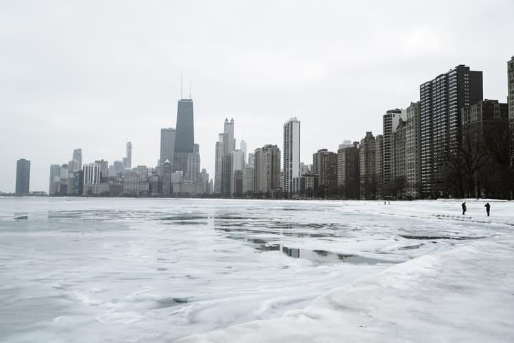 Shoreline of a city and a semi frozen lake