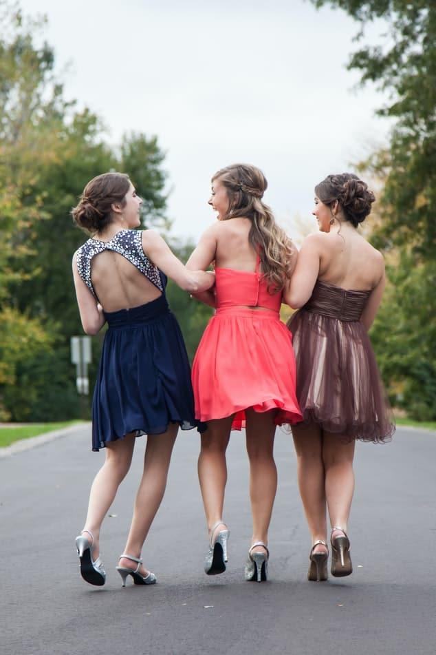 Three girls in formal wear walking up the street