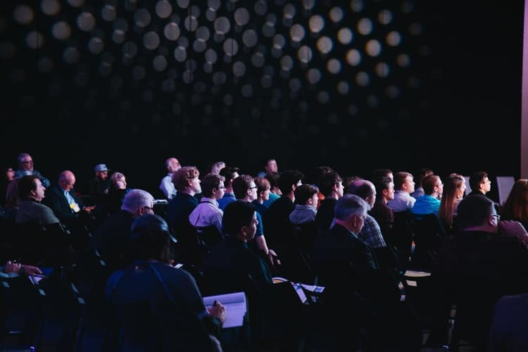 Several people sitting in a dark room representing employees at a conference